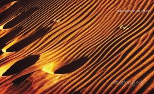 As footprints mark the arid desert dunes,看到足印在沙丘上,